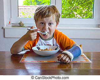 young boy with arm in cast has breakfast at the table