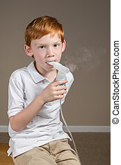Young boy with asthma completing a breathing treatment