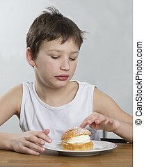 Young boy with cream bun