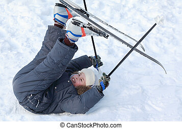 Young boy with cross-country skis and poles lying on snow and put up feet on pure white snow