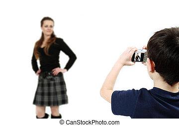 Young boy with digital camera shooting girl
