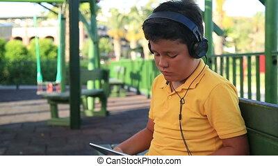 Young boy with earphone - Young boy with earphone using...