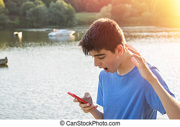 young boy with expression of surprise with the mobile phone outdoors