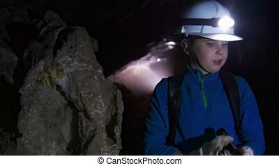 Young boy with flashlight examines the cave, close up