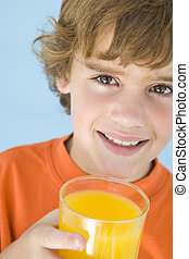 Young boy with glass of orange juice smiling