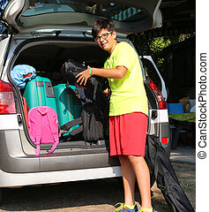 boy with glasses loads the luggage in the trunk of the car