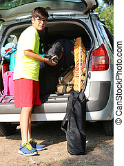 young boy with glasses loads the luggage in the trunk of the car