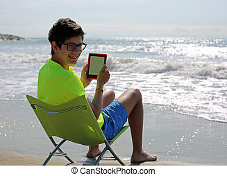 boy with glasses reads an ebook on the beach