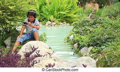 Young boy with hadphones gaming on smartphone