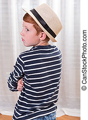 young boy with hat looking over his shoulder