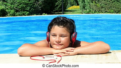 Young boy with headphone relaxing in the pool - Happy...