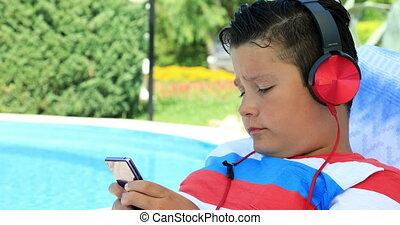 Young boy with headphone using smartphone