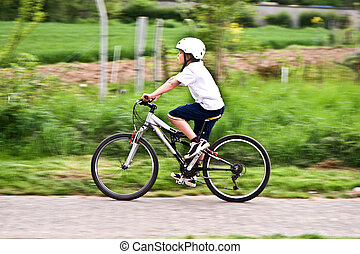young boy with helmet is riding mountain bike