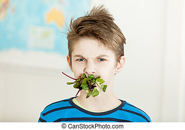Young boy with his mouth stuffed with baby spinach