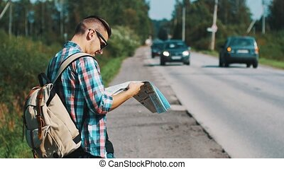 Young boy with map and backpack stay at road in summer sunny day. Tourist. Cars.