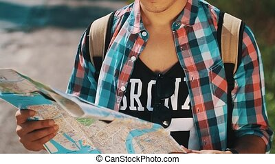 Young boy with map hitchhiking at road in summer sunny day. Tourist. Backpack
