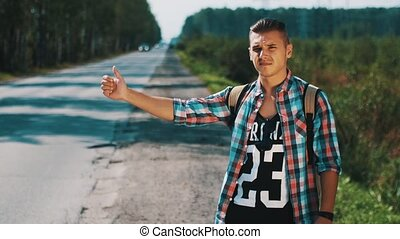 Young boy with map hitchhiking at road in sunny day. Tourist. Thumb up. Backpack