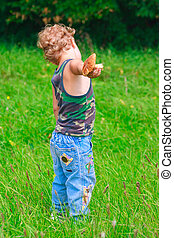 Young boy with mushroom in a meadow