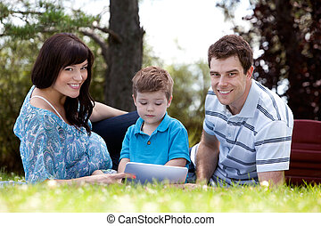 Young Boy With Parents in Park