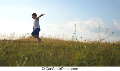 Young boy with raised hands running on green grass at the field on sunny day. Child jogging at the lawn outdoor. Happy smiling male kid having fun in nature on a summer meadow. Slow motion Close up