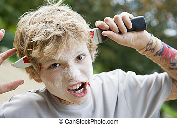 Young boy with scary Halloween make up and plastic knife through