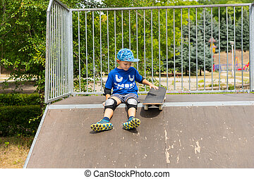 Young Boy with Skateboard Sitting on Ramp