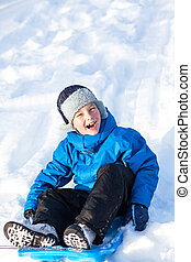 A young boy shows his excitement sledding in winter.