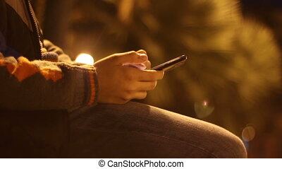Young boy with smartphone in a city park at night