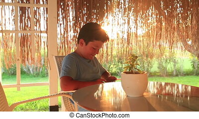 Young boy with smartphone in summer cafe