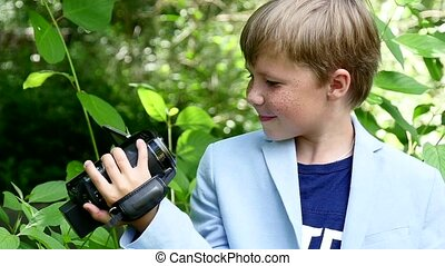 Young boy with video camera shoots film in nature of green park slow motion.