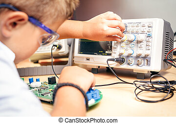 Young boy working on an electronics project