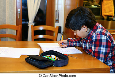 young boy writes on his notebook at home 7