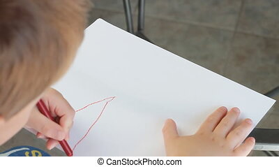 Young Boy Writing ABC On A Sheet Of White Paper With A Crayon