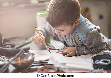 Young boy writing words in a notebook