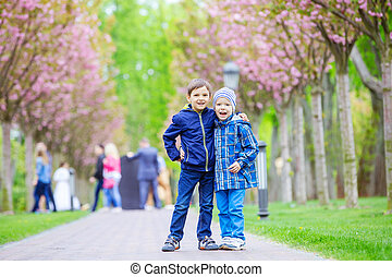 Young boys smiling while standing on lane in park