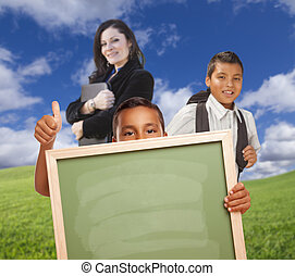 Young Boys with Blank Chalk Board, Teacher Behind on Grass