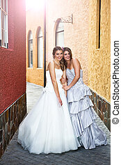 A young bride and her bridesmaid smile at the camera while walking in an alley. Vertical shot.