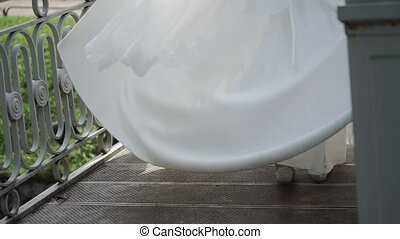 Young bride circling ahead groom in park slow motion, waving her white bridal dress