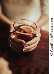 Young bride drinking tea. Wedding bouquet on a wooden table in a restaurant. Cropped image of bride which holding a cup of tea with lamon