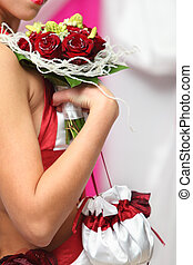 young bride hand holds bouquet of red roses and white silk reticule