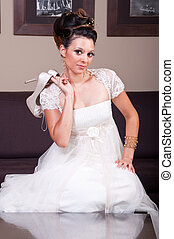 young bride holding shoes