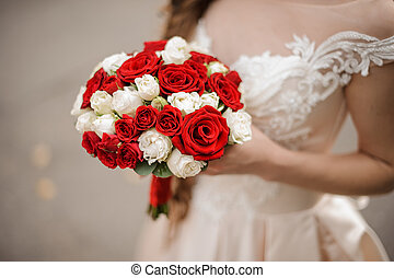 Young bride in a wedding dress holding a bouquet of white and red roses