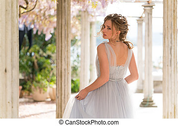 young bride in a wedding dress poses on the terrace