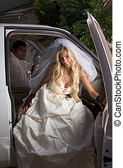 Young bride in wedding dress getting off car