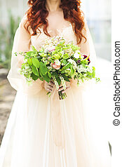 Young bride in wedding dress holding beautiful bouquet