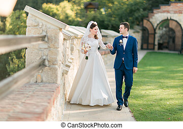 Young bride in white dress and groom walking holding hands near old castle