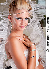 Young bride in white dress with tiara and veil