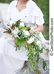 Young bride in white wedding dress holding beautiful bouquet
