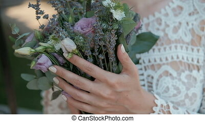 Young bride is holding bouquet of flowers in hands standing...