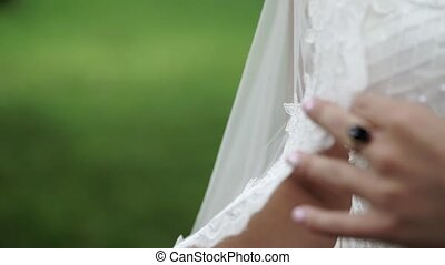 Young bride posing in a park, waving veil veil slowmotion